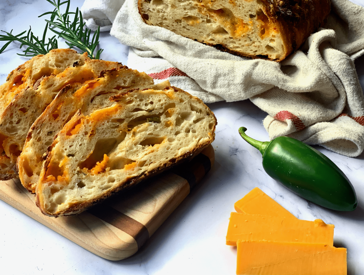 Four slices of cheddar-jalapeno bread with nice big air pockets sit on a small wooden cutting board on the left side of the photo. Two sprigs of rosemary are behind the cutting board. In the top center-right of the photo is the other half of the loaf, sitting on a white towel with a red stripe. In the bottom right of photo is a whole jalapeno and three slices of cheddar cheese.
