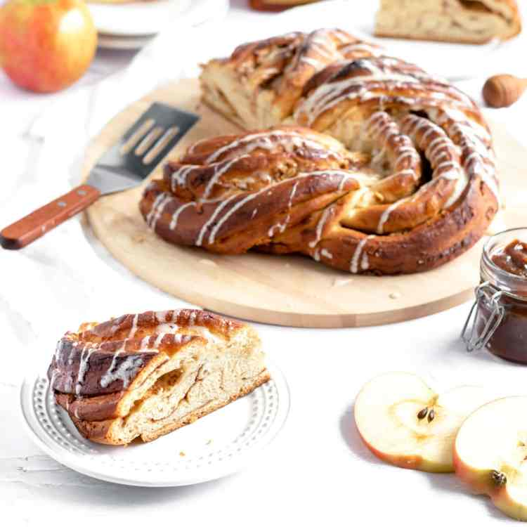 An overhead shot of an apples and honey babka on a cooling rack. To the left of the cooling rack is a small apple that's been cut in half. Above the cooling rack to the right of the apple is a bottle of honey. To the right of the bottle of honey is a small whole apple, stem intact.
