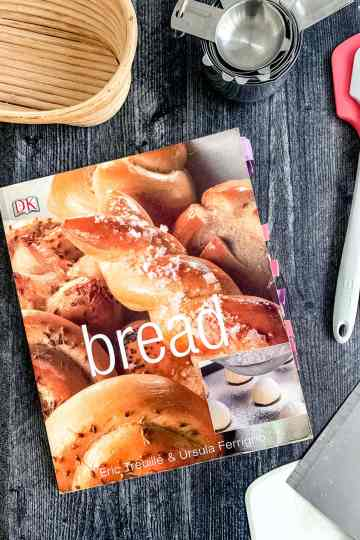 the bread book sits on a counter near a wicker brotform, two spatulas, a set of measuring cups, and a bench scraper