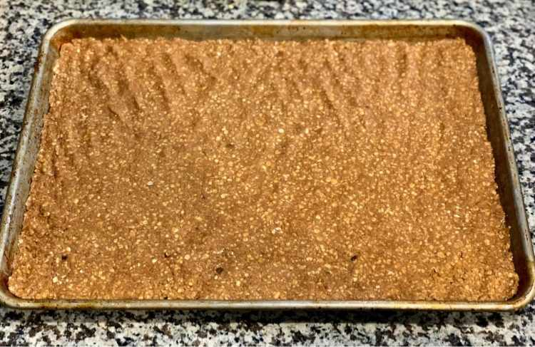 An 18 by 13 inch sheet pan sits on a grey and white kitchen counter. The sheet pan has a layer of golden brown oatmeal dough pressed into every corner and to every edge. Fingerprint divots are visible across the surface.