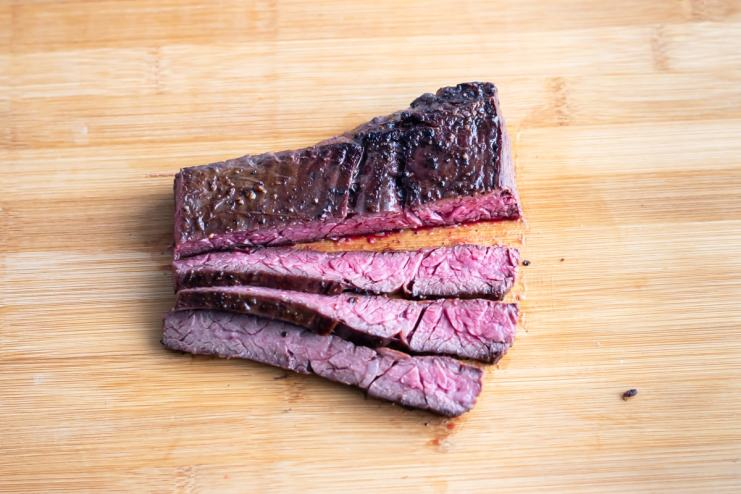 An overhead shot of a cooked flap steak. the steak has been cut in half down the middle. One half has been sliced across the grain into thin quarter in ch strips. The edge of a knife blade sticks into the top right corner of the photo.