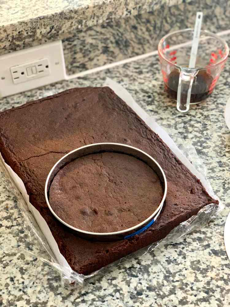 A rectangular chocolate cake sits on a counter. A 6 inch metal cake cutting ring has been pressed through the bottom left corner of the cake. On the counter in the top right of the photo is a 1 cup measuring cup with a coffee soak in it. A small measuring spoon sits inside the cup.