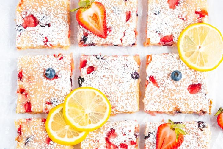 an overhead shot of 9 blondies arranged in a 3 by 3 grid. to the left is a small bowl of blueberries. lemon slices and strawberry pieces decorate the blondies.