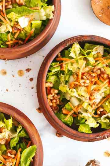three bowls of lettuce and walnut salad shot overhead. a large wooden spoon sits to the right and a silver fork sits to the left.