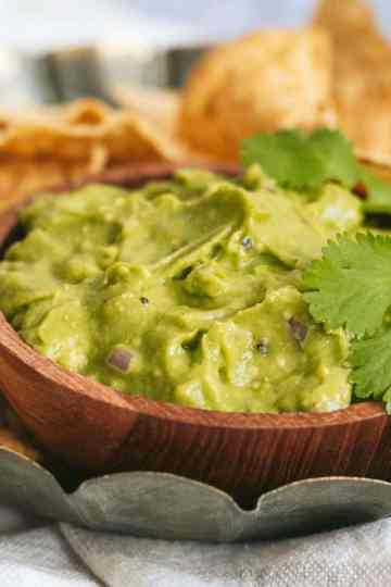 a small dish of guacamole sits in a metal serving bowl surrounded by tortilla chips