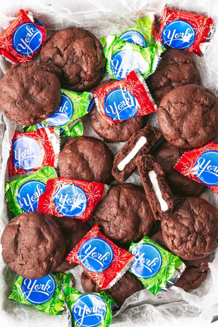 Peppermint patty stuffed brownie cookies on a sheet pan with red and green wrapped peppermint patties. One cookie has been broken in half, revealing a white strip of peppermint patty filling inside.