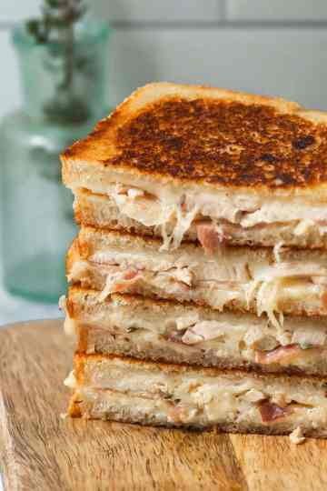 a stack of grilled cheese chicken cordon bleu sandwich halves on a wooden cutting board.