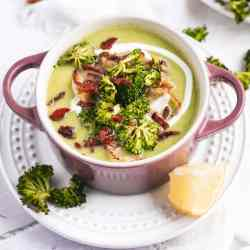 a close up of a purple ramekin filled with broccoli soup