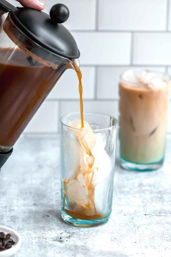 Cold brew coffee being poured from a french press into a tall aqua-tinted glass filled with ice. another glass of iced coffee is visible behind it.