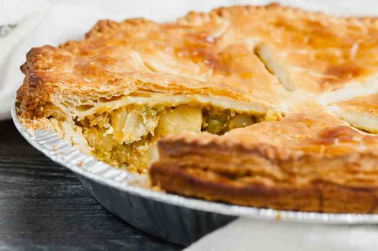 a close up of the samosa pot pie from the side. a slice has been cut out and the pea and potato filling is visible.
