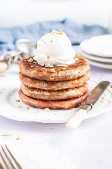 a stack of brown butter cinnamon roll pancakes on a plate topped with a scoop of vanilla ice cream