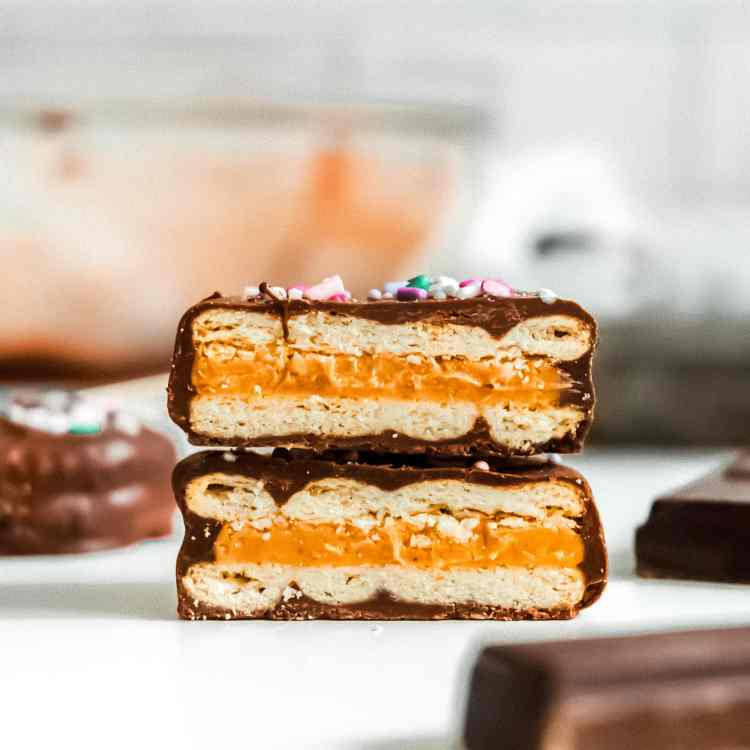 a close up straight on shot of two halves of a patty cake stacked on top of each other revealing the layers of ritz cracker and peanut butter inside the chocolatey shell