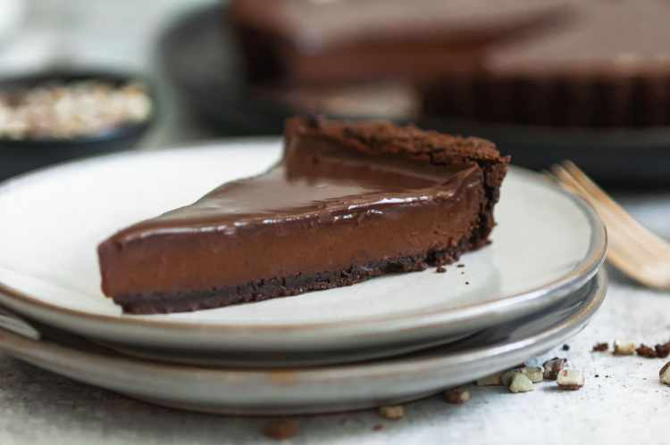 a close up of a single slice of chocolate tart on a small plate, showing the three layers of chocolate: cookie crust, ganache filling, and glaze