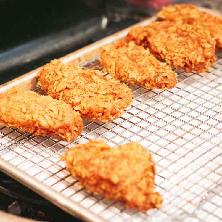 a row of chicken tenders arranged on a wire cooling rack over a paper towel immediately after coming out of the frying pan