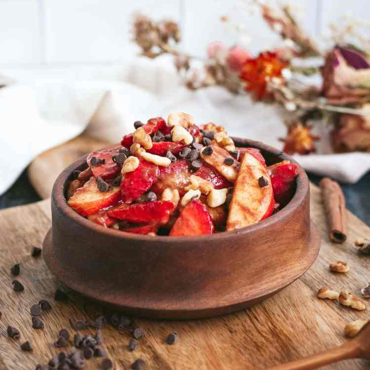 a wooden bowl filled with fruit salad sits on a wooden board. a napkin and dried flowers are visible behind it. the fruit salad is garnished with mini chocolate chips and chopped walnuts.