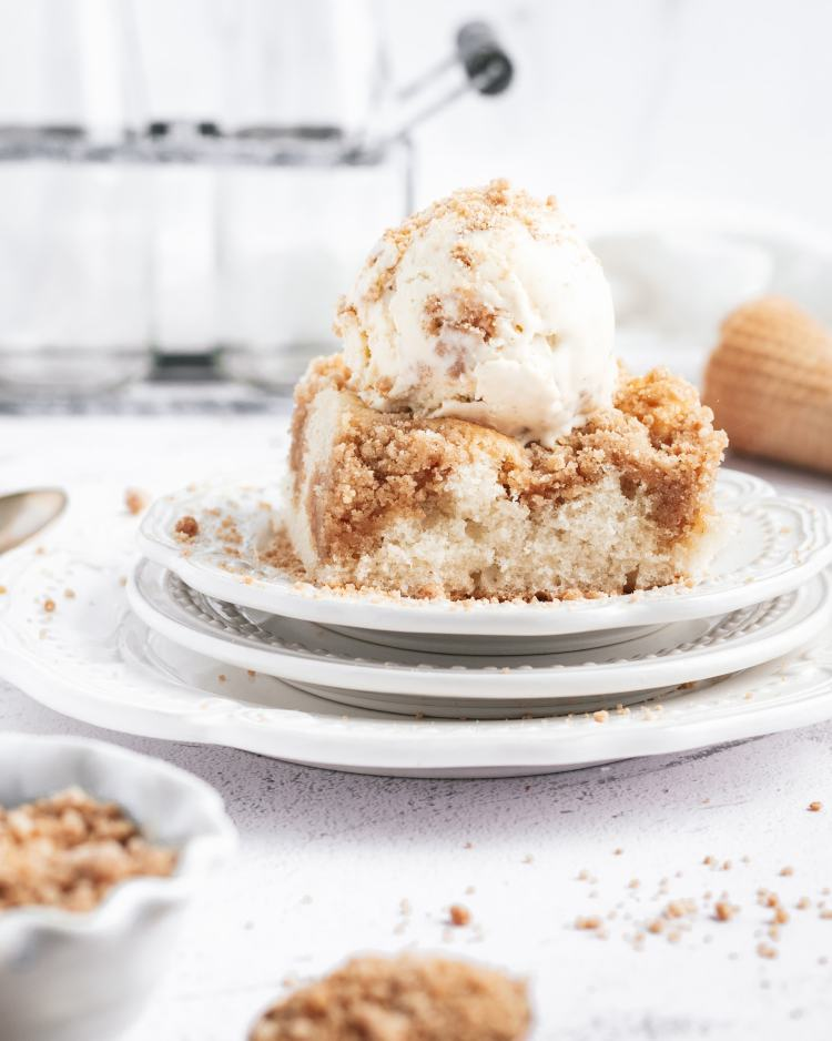 a scoop of crumb cake ice cream on top of a slice of crumb cake on a plate