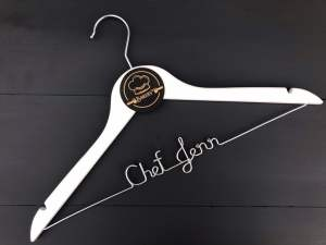 """a white wooden hanger that has a wire bar across the bottom bent to spell out """"chef jenn"""""""