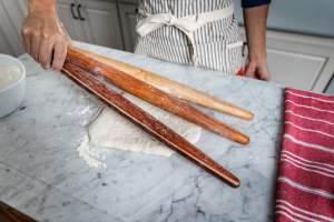 a baker holding three french rolling pins by one end on a floured countertop