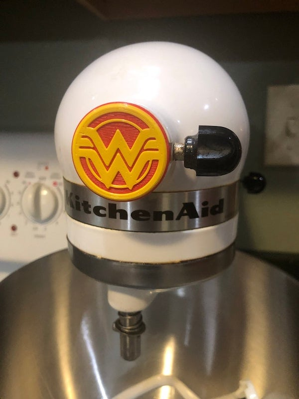 the front of a white kitchen aid mixer with a wonder woman decal in the front
