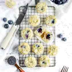 an overhead shot of mini muffins on a cooling rack. one has been split open revealing a blueberry center.