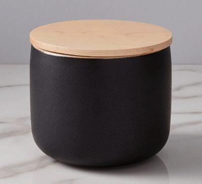 a black container with rounded bottom and straight sides and flat wooden lid