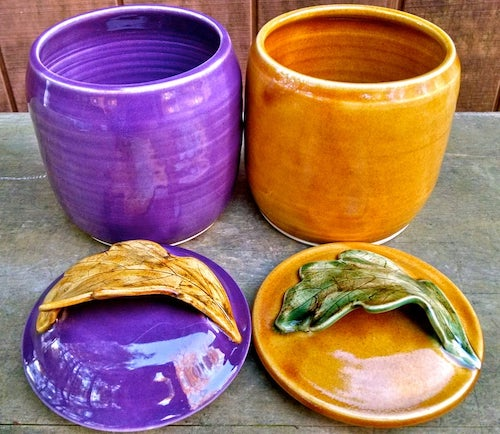 a purple and orange sourdough crock sit side by side. their lids have leaves as handles and sit in front of them.
