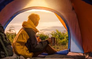Young man sitting in the tent holding a cup, looking from afar