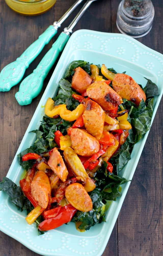 A healthy kale salad topped with chicken sausages, peppers, and a delicious honey mustard dressing! #kale
