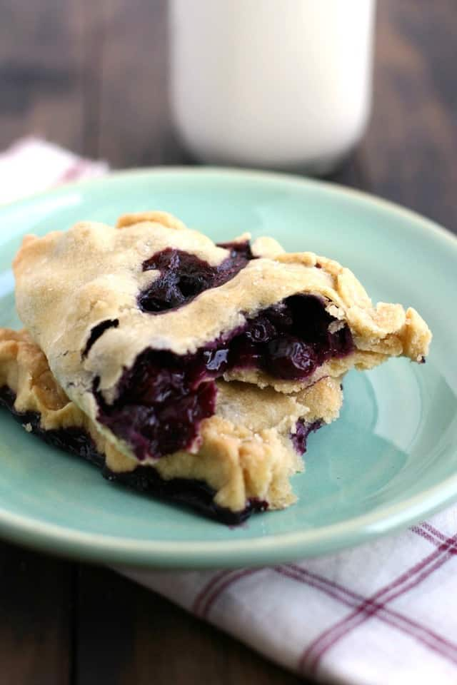 Tasty blueberry hand pies are a must make dessert this summer! You won't believe how SCRUMPTIOUS summer berries taste when wrapped in this flaky crust! Portable and delicious. #blueberry