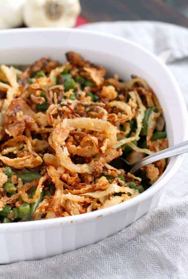 This delicious gluten free green bean casserole is topped with homemade french fried onions. Perfect for a holiday meal!