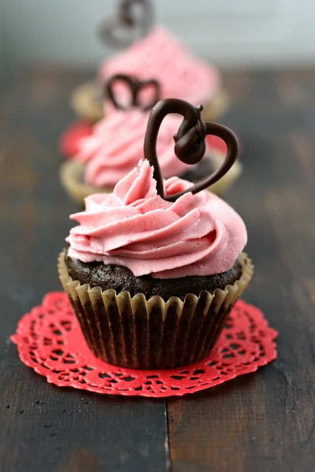 Rich chocolate cupcakes are topped with naturally dyed pink frosting and chocolate hearts. These are pretty and delicious!