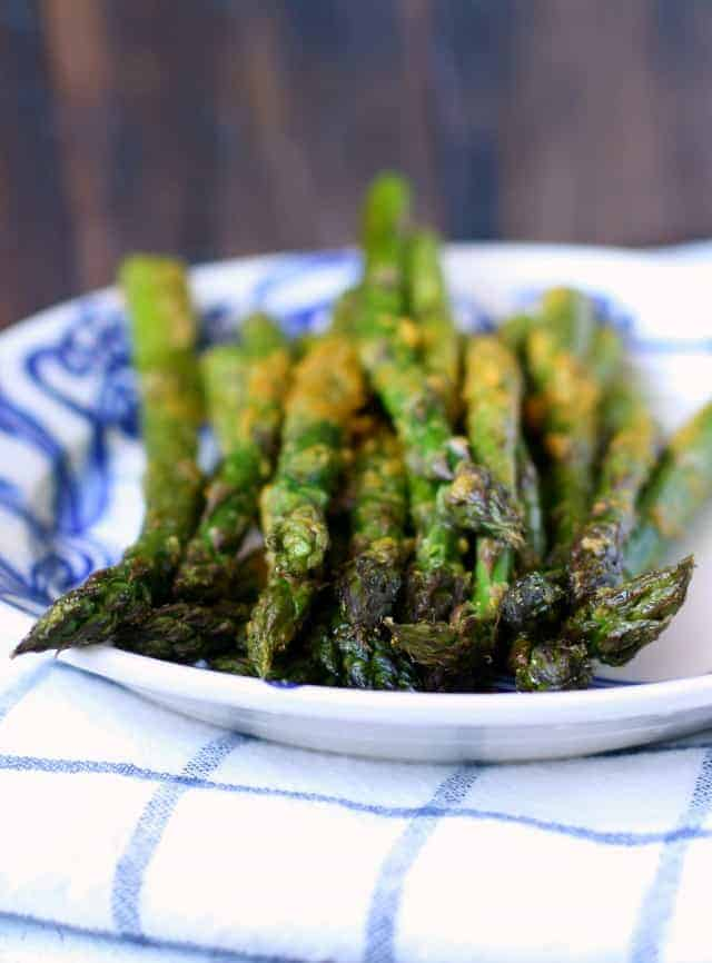 Fresh asparagus is coated with a cheesy, buttery topping - a tasty vegan side dish!