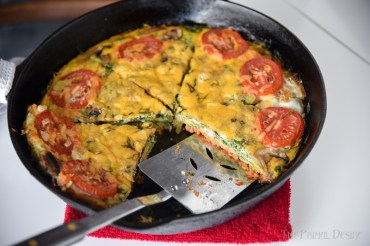Cast iron pan with Keto Salmon Frittata topped with cheese and tomatoes.