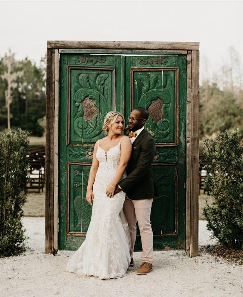 Married couple posing in front of green door