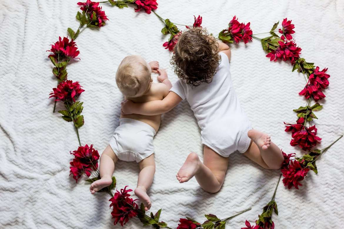 A baby and toddler are laying on their fronts on a white bed. The toddler has their arm around the the baby. The baby is in a white nappy and the toddler is wearing a white baby grow. Around them is lots of red flowers in the shape of a heart