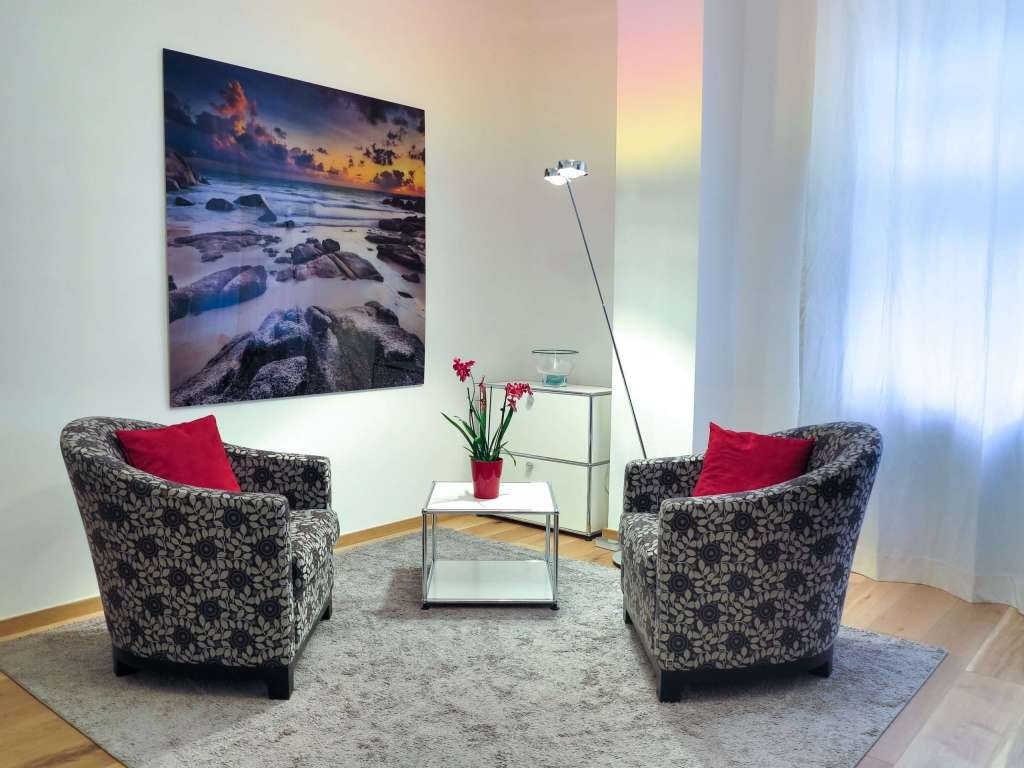 2 black and white armchairs in a small room with red pillows. Painting on the wall of a sunset. There is a big window with a white net curtain