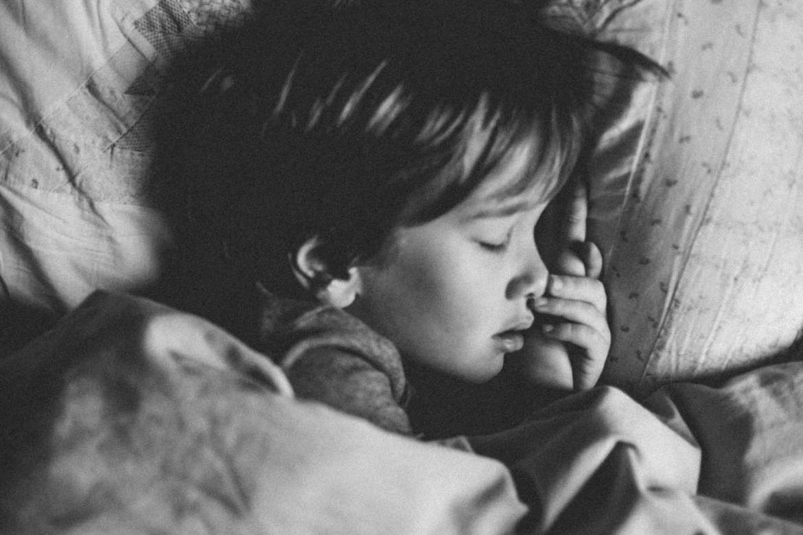 A black and white picture of a child sleeping in their bed