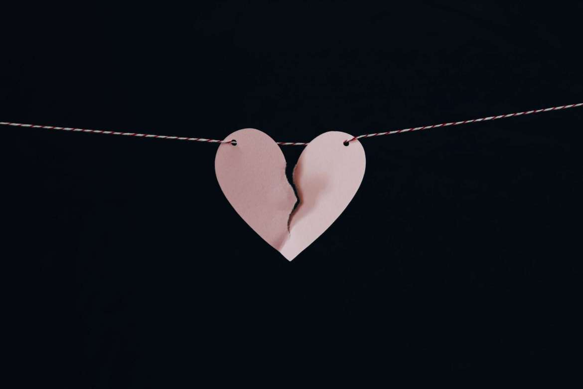 A black background. A pink paper heart on a red and white string is almost torn in half.