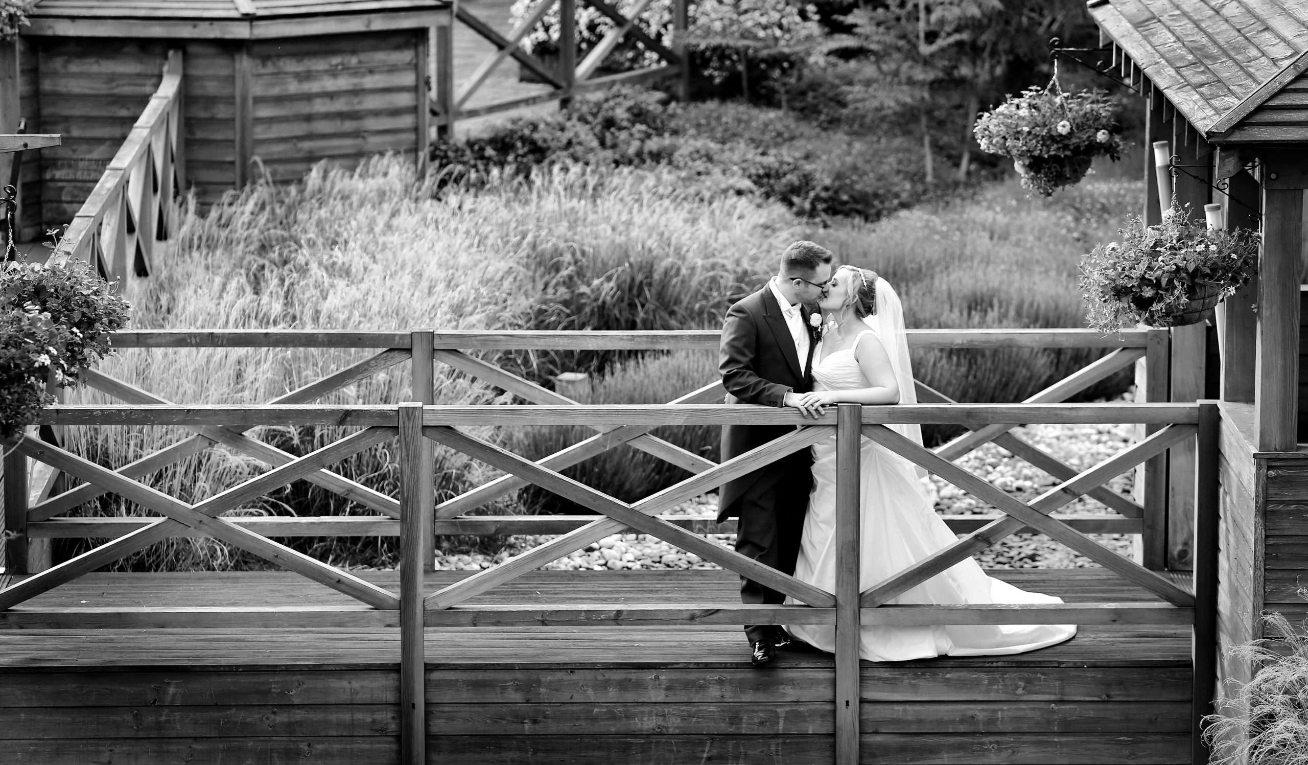 Black and white photo of Lisa and Darren on their wedding day. They are stood on a wooden walkway and are kissing