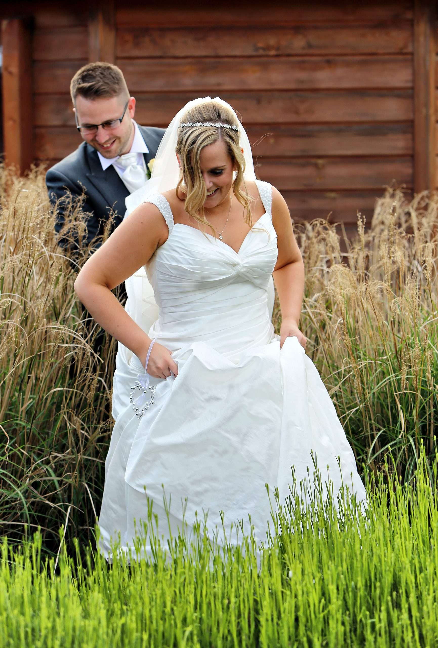 Lisa and Darren are in their wedding clothes. They are walking through tall grass