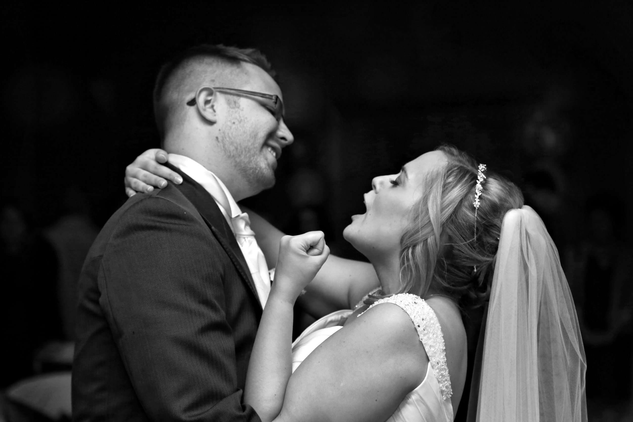 Black and White photo of Lisa and Darren in their wedding clothes. they are dancing and Lisa has her mouth open, singing with her fist pumped