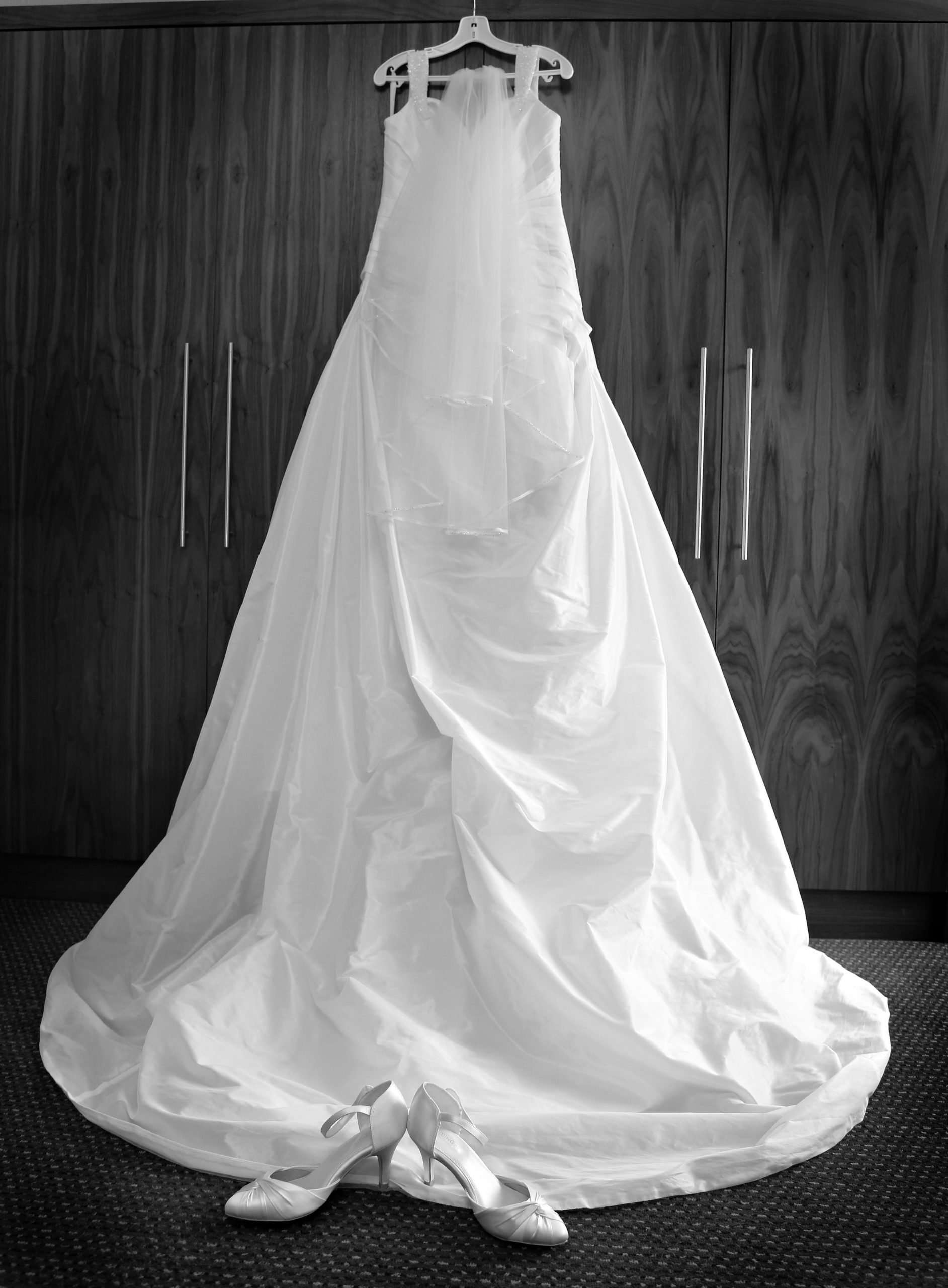 Black and white photo of Lisa's wedding dress hung up with there veil and her shoes are underneath