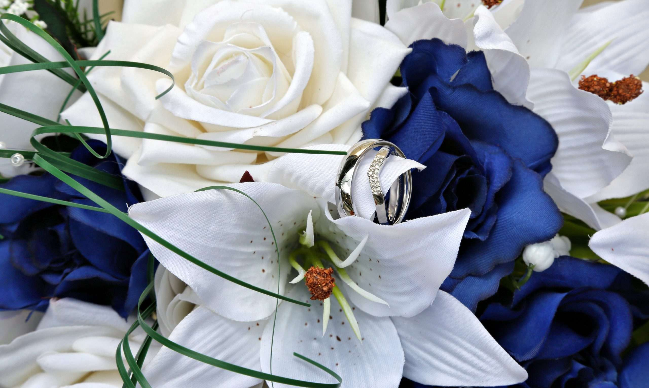 Close up of fake blue and white flowers with Darren and Lisa's wedding rings on one of the petals