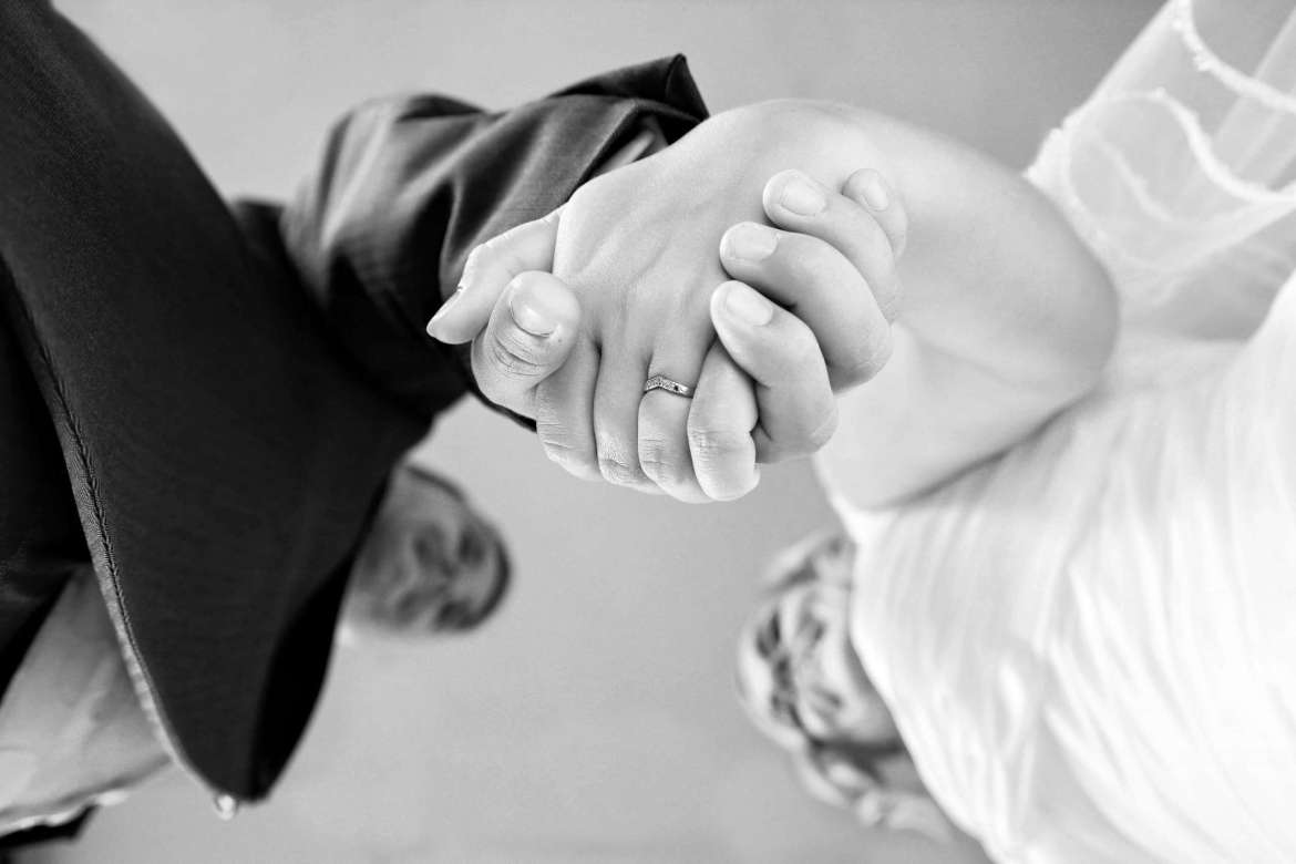 Black and White photo of Lisa and Darren holding hands on their wedding day. The photo has been taken from the floor, so their hands are in focus and their faces are out of focus