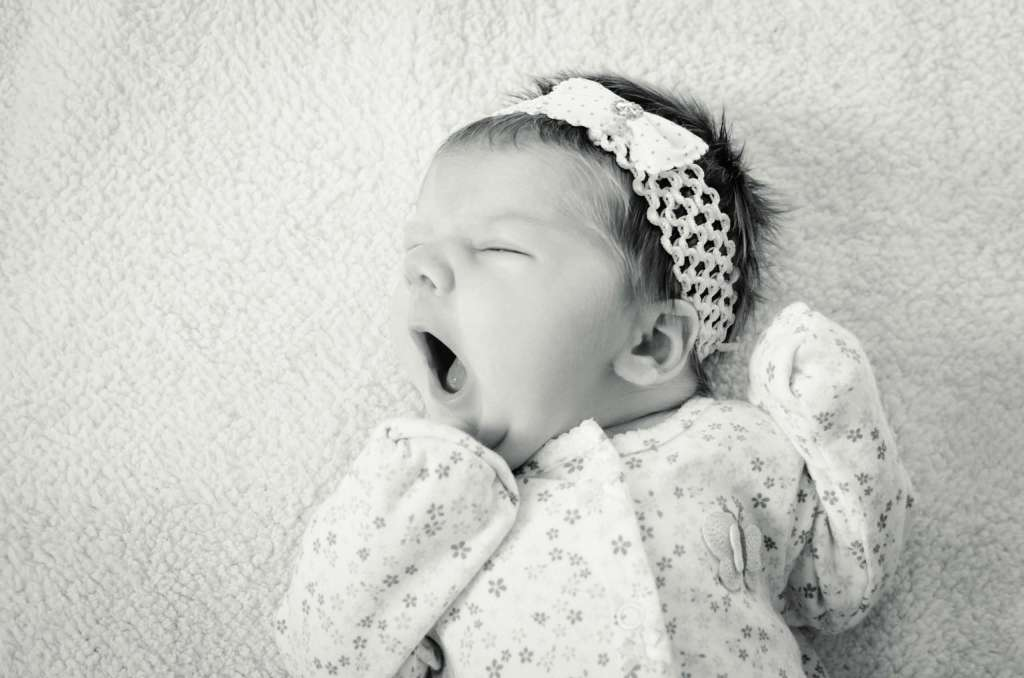 Black and white picture of a newborn baby wearing a headband yawning