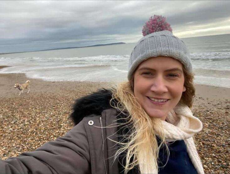 Laura on a stony beach. She is wearing a bobble hat and white scarf. She is smiling at the camera