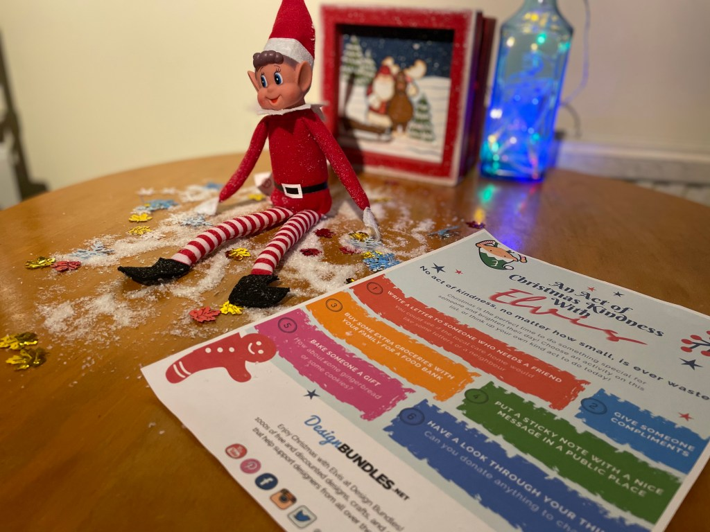 Elf on the shelf is sitting up on a wooden table. here are decorative snowflakes, snow and leaves on the table. There is a piece of paper with random asks of kindness written on it next to him