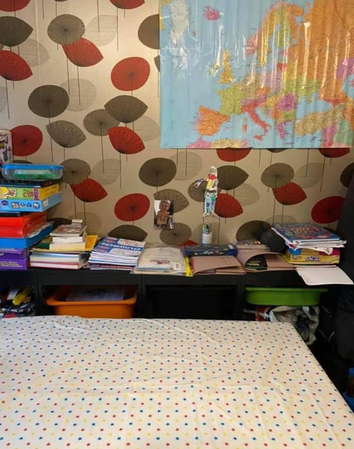 A table with a spotty table cloth is in front of a back unit with school books. There is a map of the world on the wall. The wallpaper is red and green flowers on a beige background