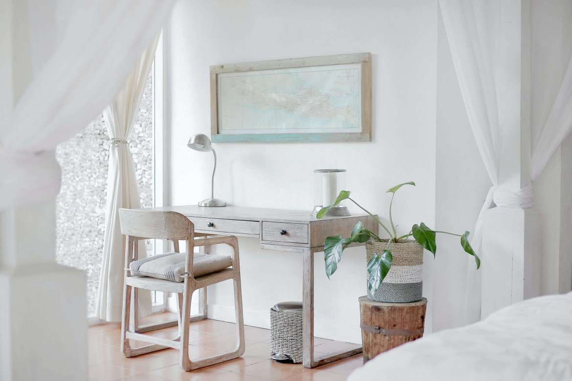 A white bedroom/office with white curtains hung up. There is a pale wooden desk with a lamp on it. A plant pot with a green plant is next to the desk