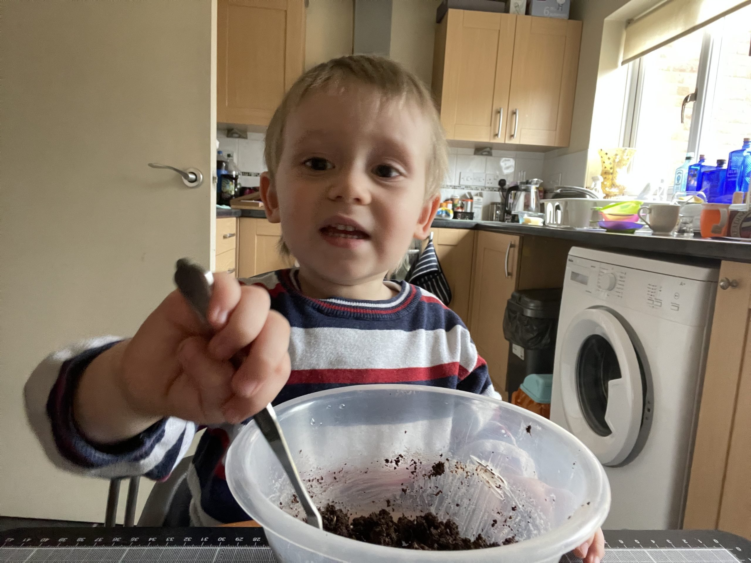 Little J is wearing a white, red and blue jumper. He is sat at a table with a bowl in front of him. There is compost and clay in the bowl and he is stirring it with a metal spoon. He is smiling at the camera